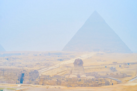 The foggy morning in Giza Necropolis with a view on Pyramid of Khafre and Great Sphinx, the wind carries the clouds of desert sand, Cairo, Egypt. Stock Photo