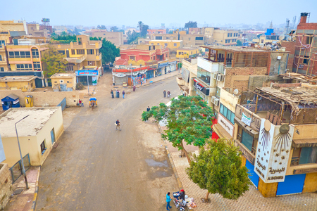 GIZA, EGYPT - DECEMBER 20, 2017: The urban scene of Giza town with old residential houses, numerous tourist cafes and street food vendor, selling food for locals, on December 20 in Giza