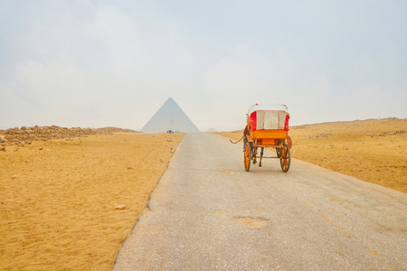 The old horse drawn carriage is the best and the most comfortable way to explore large desert archaeological site of Giza, Egypt