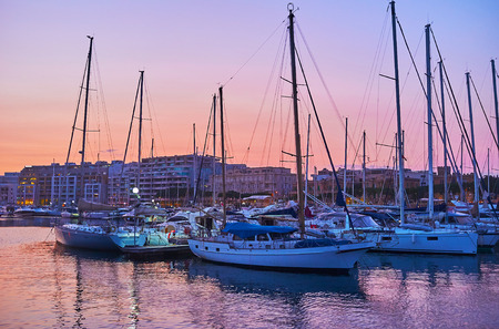 The lines of moored yachts in marina of Msida with a view on bright twilight sky on background, Malta.
