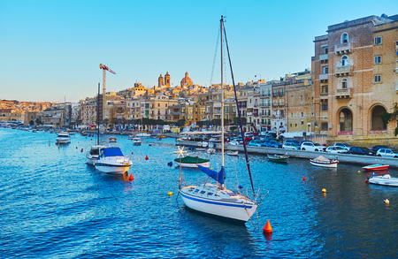 The pleasant trip around medieval cities of Valletta Grand Harbour, numerous fishing boats and luzzu are moored at the shore of L-Isla, Senglea, Malta. Banque d'images