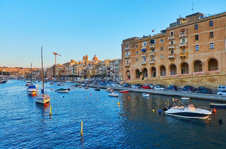 The yachts and luzzu boats at the shore of fortified L-Isla, one of the stunning medieval cities of Valletta Grand Harbour, Senglea, Malta.