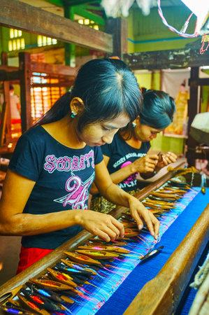 MANDALAY, MYANMAR - 21 FÉVRIER 2018 : Les artisans travaillent avec des fils de soie colorés au métier à main, le 21 février à Mandalay.