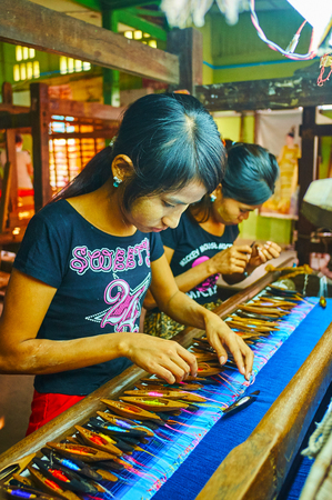 MANDALAY, MYANMAR - FEBRUARY 21, 2018: The artisans work with colorful silk threads at the handloom, on February 21 in Mandalay. Editorial