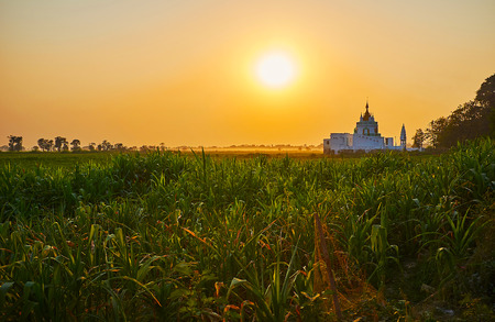 The bright sunset above the farmlands of Amarapura, the hazy Shwe Modeptaw Pagoda  dominates the plain, Myanmar.