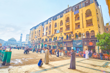 CAIRO, EGYPT - DECEMBER 20, 2017: The line of tourist restaurants in ground floor of historical edifice in busy Midan Hussein Square, on December 20 in Cairo.