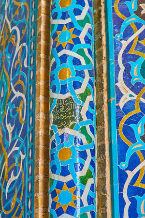 YAZD, IRAN - OCTOBER 18, 2017: The close-up of the slender column of Jameh Mosque's mihrab with fine Islamic patterns of tiles and intricate calligraphy in octagonal star in the middle, on October 18 in Yazd.