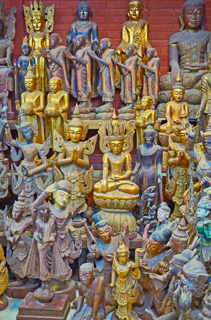 The ornate wooden sculptures of Buddha, his disciples, Nat deities and mythic creatures in workshop of Shwe-gui-do quarter, Mandalay, Myanmar. Stock Photo
