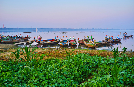 The green bank of Taungthaman Lake with a view on traditional wooden canoes, decorated with painted elements, Amarapura, Myanmar.