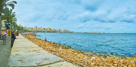 ALEXANDRIA, EGYPT - DECEMBER 19, 2017: Panorama of the long coastline of the city and line of palm trees in Corniche Avenue, on December 19 in Alexandria.