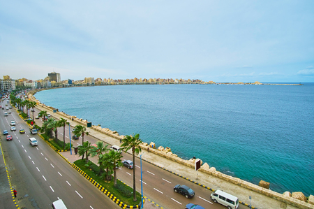 Enjoy the scenic view of Alexandria coastal district with noisy Corniche Avenue, stretching to the Qaitbay Citadel, seen on horizon, Egypt.
