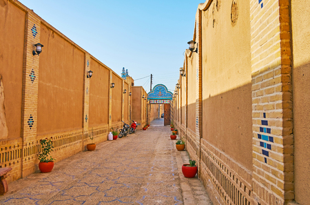 YAZD, IRAN, OCTOBER 18, 2017: The long narrow inner court of historic mansion of Yazd Bar Association with adobe walls, decorated with brickwork and geometric tile patterns, on October 18 in Yazd.