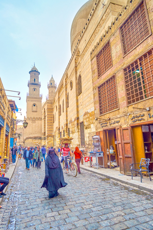 CAIRO, EGYPT - DECEMBER 20, 2017: The woman in traditional abaya dress walks along historical Al-Muizz street, passing small shops and cafes, on December 20 in Cairo. Editorial