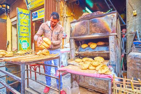 Kairo, Ägypten - 20. Dezember 2017: Der Bäcker verkauft das heiße frische Fladenbrot in der El Gamaleya Straße, Khan El Khalili Basar, islamisches Kairo, am 20. Dezember in Kairo.