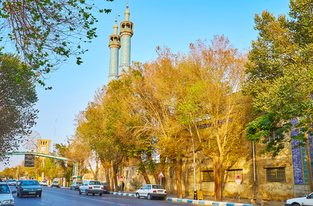 YAZD, IRAN - OCTOBER 18, 2017: The lush shady trees line Imam Khomeini street, the tall twin minarets of Rozeh Mohamadieh Mosque (Hazireh) are seen on the background, on October 18 in Yazd