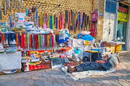YAZD, IRAN - OCTOBER 18, 2017: The elderly merchant sleeps on the floor during the afternoon siesta at his small outdoor stall of shoe care products and accessories in the street of Khan Bazaar, on October 18 in Yazd. Sajtókép