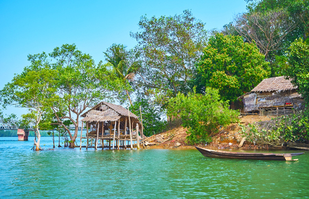 The old nipa hut of the local fishermen at the green bank of Kangy river, Chaung Tha zone, Myanmar.