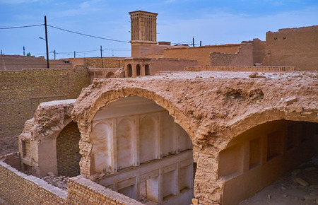 The ruined roof and side wall of the medieval mansion in old Yazd open the view on preseved parts of its rooms, Iran.