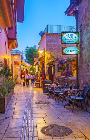 ANTALYA, TURKEY - MAY 9, 2017: The cozy narrow street in Kaleici district with historic townhouses, tiny gardens, atmospheric music and large amount of small cafes and bars, on May 9 in Antalya. Imagens - 115577250