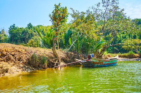 The old fishing boat is moored at the green bank of Kangy river, Chaung Tha zone, Myanmar.