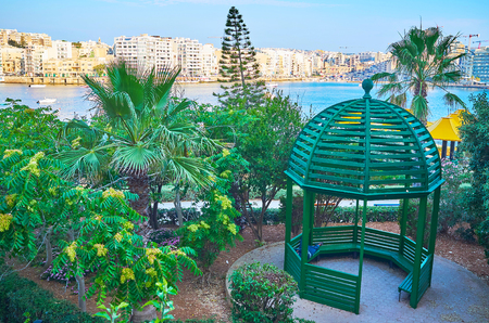 The wooden alcove in beautiful Independence garden on Sliema coast with a view on St Julian's town across Exiles Bay, Malta.