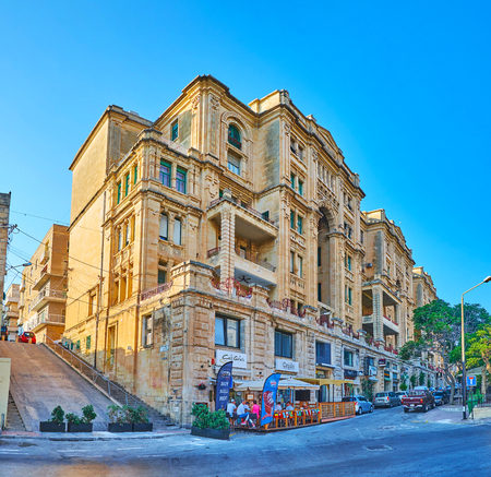 ST JULIANS, MALTA - JUNE 20, 2018: The scenic historical mansion in old quarter at Balluta Bay with outdoor cafe and fashion boutiques, on June 20 in St Julians.