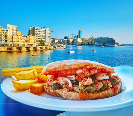Enjoy delicious tuna sandwich with tomato, capers, sweet onion and French fries in outdoor cafe of Sliema, located at the Exiles Bay, Malta. Фото со стока