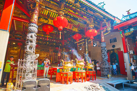 YANGON, MYANMAR - FEBRUARY 17, 2018: The inner yard of Kheng Hock Keong Temple with carved wooden columns, large red lanterns and the fuming incense sticks in gilt vases, on February 17 in Yangon. Redactioneel