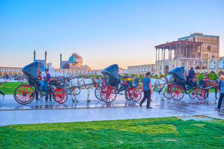 ISFAHAN, IRAN - OCTOBER 19, 2017: The line of horse drawn carriages in Naqsh-e Jahan Square wait for clients, on October 19 in Isfahan