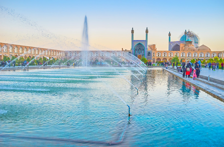 ISFAHAN, IRAN - OCTOBER 19, 2017: Evening is the most busiest time in Nashq-e Jahad Square, locals walk and rest on the benches or steps of the central pool with a fountain, on October 19 in Isfahan Editorial