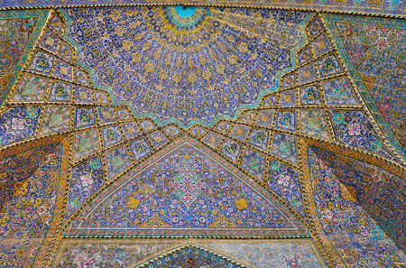 ISFAHAN, IRAN - OCTOBER 21, 2017: The colorful semi-dome and muqarnas (honeycomb) details of Seyed Mosque, covered with intricate tile patterns on floral themes, on October 21 in Isfahan. Editorial