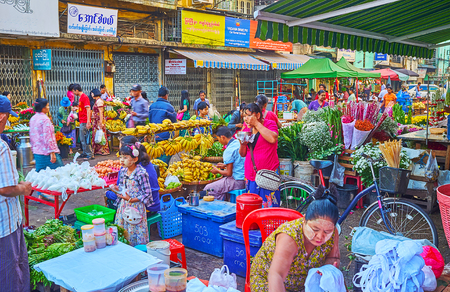 YANGON, MYANMAR - FEBRUARY 15, 2018: The crowded street of morning Chinatown market with densely sandwiched fruit and flower stalls, on February 15 in Yangon.