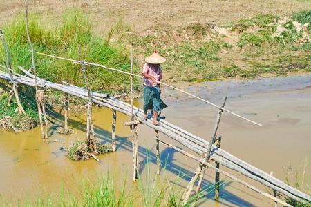 Burmese peasant in conical hat crosses primitive bamboo footbridge over the canal of Bago river, Bago suburb, Myanmar.