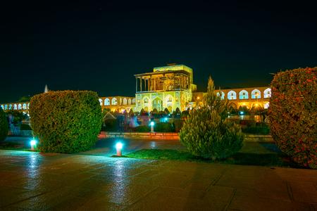 The pleasant evening in Nashq-e Jahad Square with beautifully illuminated Ali Qapu Palace, Isfahan, Iran