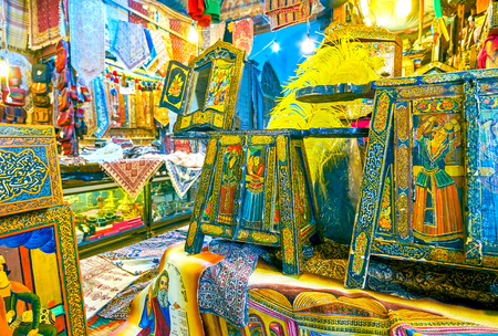 ISFAHAN, IRAN - OCTOBER 19, 2017: The old wooden furniture with traditional paintings in small souvenir shop in Grand Bazaar, on October 19 in Isfahan Standard-Bild - 115713243