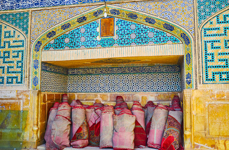 The niche in wall of the West portal of Jameh Mosque with rolls of prayer mats, Isfahan, Iran.