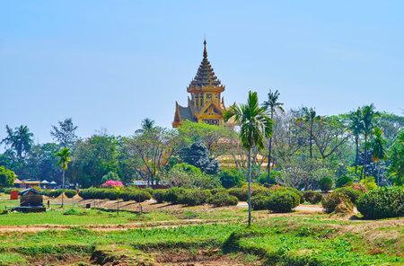The lush greenery of the Royal garden hides the ornate gilded building of Bhammayarthana Throne Hall (Bee Hall) of Kanbawzathadi palace, Bago (Pegu), Myanmar.