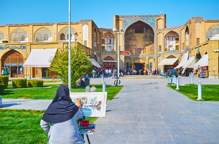 ISFAHAN, IRAN - OCTOBER 21, 2017: The watercolor artist works in Naqsh-e Jahan Square, making the sketch of Qeysarie Gate of Grand (Soltani) Bazaar, on October 21 in Isfahan. Editorial