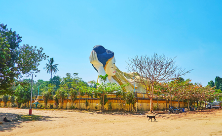 The giant statue of Lying (Reclining) Buddha on the pedestal, surounded by green garden, Mya Tha Lyaung Buddha Temple, Bago, Myanmar.