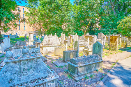 The historical Old Jewish Cemetery in Kazimierz district surrounded with lush garden and shady trees, Krakow, Poland