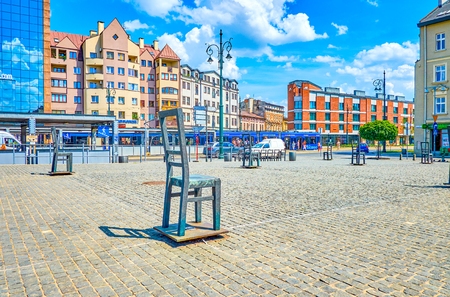 KRAKOW, POLAND - JUNE 21, 2018: Square of Ghetto Heroes with Empty Chairs memorial of Jewish victims in World War 2, the busy city road with fast traffic is seen on background, on June 21 in Krakow.