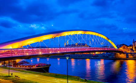 The colorful evening illumination of modern Father Bernatek Footbridge, and moored large boat-restaurant on the bank of Vistula river, Krakow, Poland