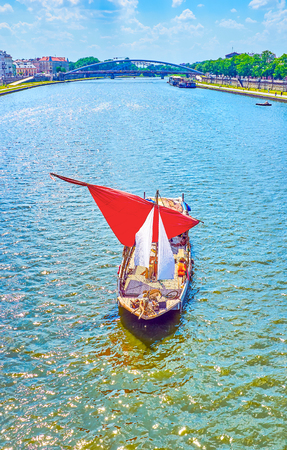 The small boat with red sail is a very popular tourist transport along Vistula River in Krakow, Poland Stock fotó