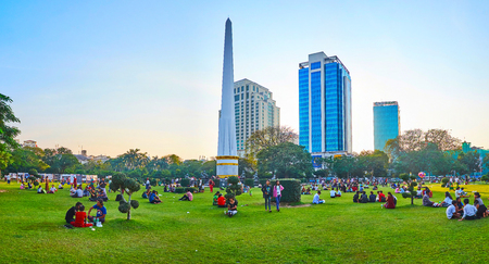 YANGON, MYANMAR - FEBRUARY 15, 2018: Panorama of crowded Maha Bandula Garden with a view on trimmed trees around the Independence Monument and tall modern buildings behind it, on February 15 in Yangon.