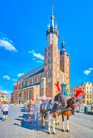KRAKOW, POLAND - JUNE 21, 2018: The Main Market Square of the city is full of tourist attractions, one of the most interesting is the riding on horse drawn carriage, on June 21 in Krakow.