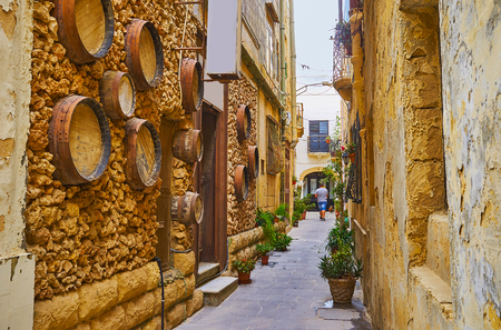 The small wine bar in the narrow backstreet of Rabat is decorated with old wooden barrels, embedded into the stone wall, Malta.