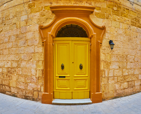 The living mansion boasts massive bright yellow wooden door with vintage door frame and metal knob knockers, Rabat, Malta.