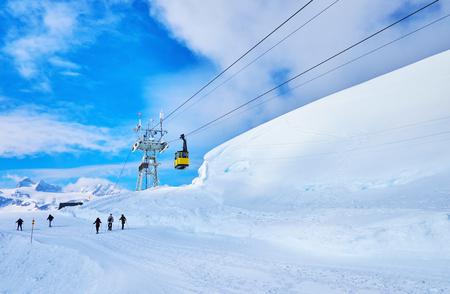 Il gruppo di racchette da neve cammina lungo la pista sul pendio del monte Krippenstein del massiccio del Dachstein con una vista sulla funivia, Obertraun, Austria.