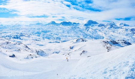 The slope of Krippenstein mount overlooks the Dachstein massif of Northern Limestone Alps with its glaciers, sharp cones, foggy peaks and best ski pistes in Salzkammergut, Obertraun, Austria.