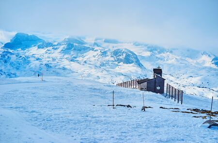 The small Berkapelle chapel is surrounded by misty snowy peaks of Dachstein massif, seen from Krippenstein mount, Salzkammergut, Austria